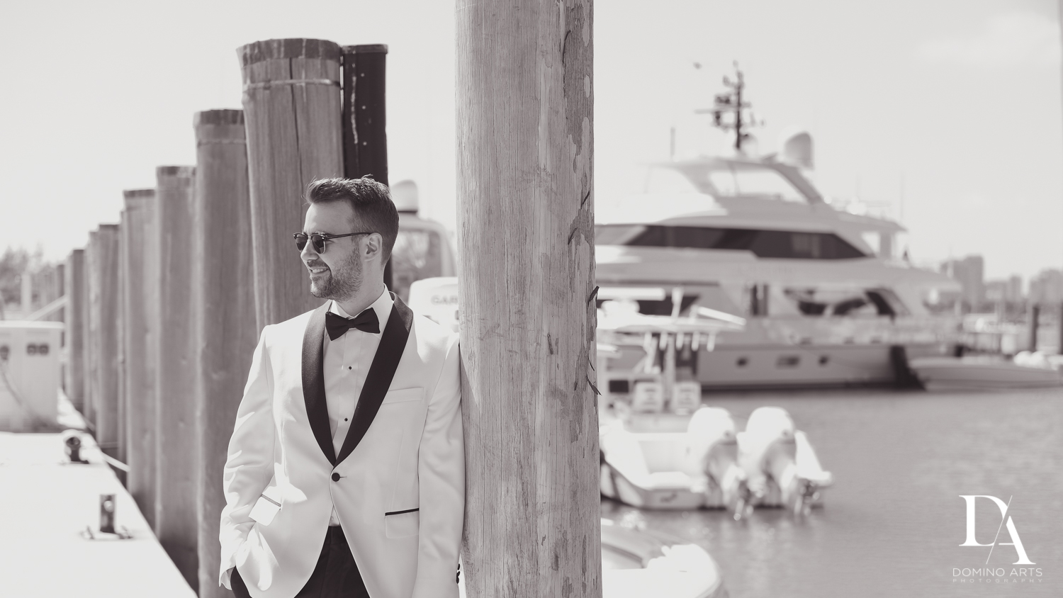 groom with yachts at Tropical Garden Wedding at Fisher Island Miami by Domino Arts Photography