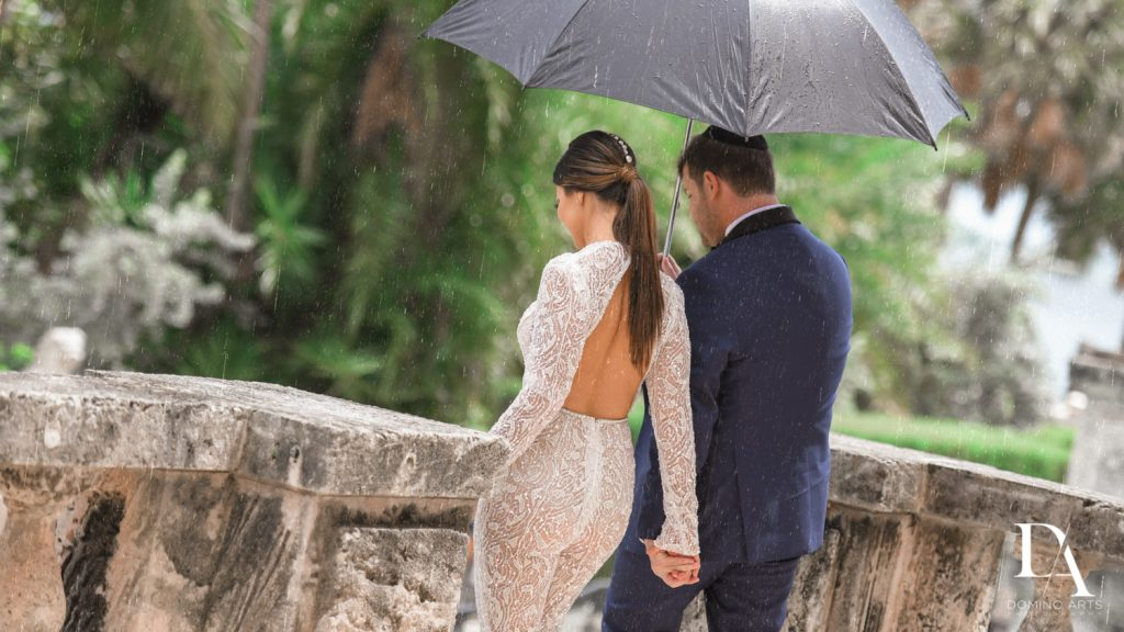 Couple under umbrella at Haute Couture Engagement Session at Vizcaya Museum and Gardens Miami by Domino Arts Photography