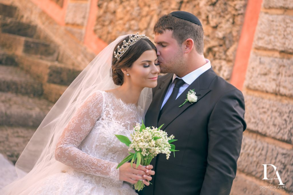 bride and groom kiss at Haute Couture Dream Wedding at Vizcaya Museum & Gardens by Domino Arts Photography