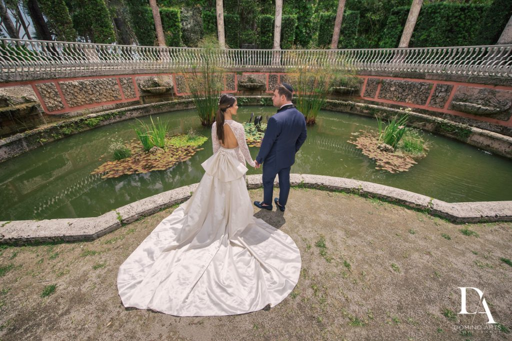 Couple by fountain at Haute Couture Engagement Session at Vizcaya Museum and Gardens Miami by Domino Arts Photography