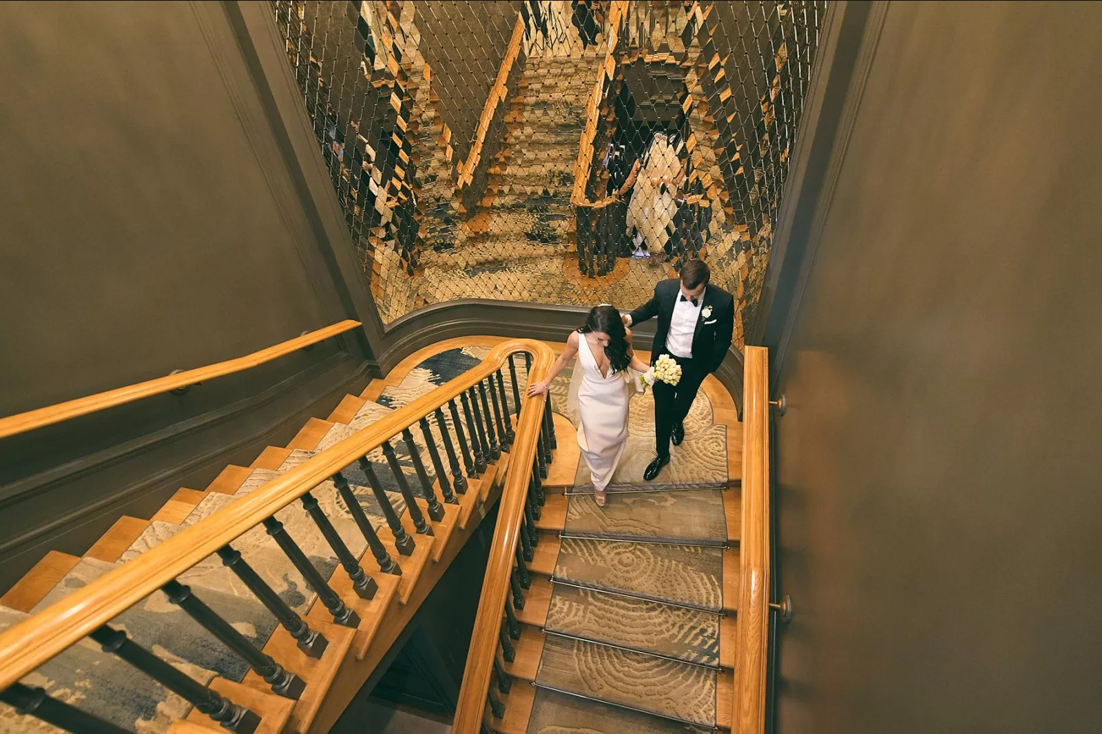 Bride and groom descending the stairs at Eau Palm Beach by Domino Arts Photography