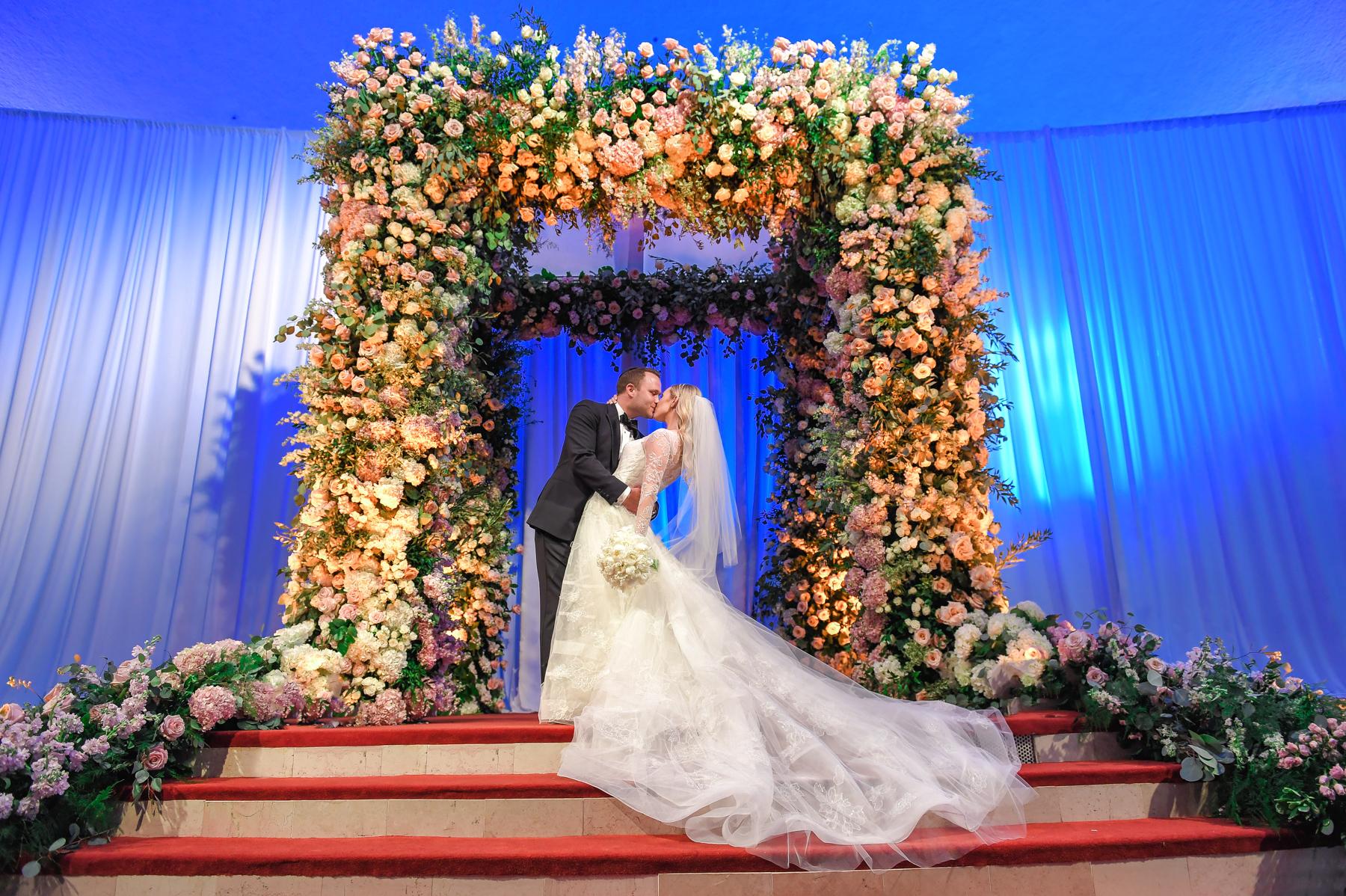 Bride and groom under a lavish chuppa at Aventura Turnberry Jewish Center & Tauber Academy