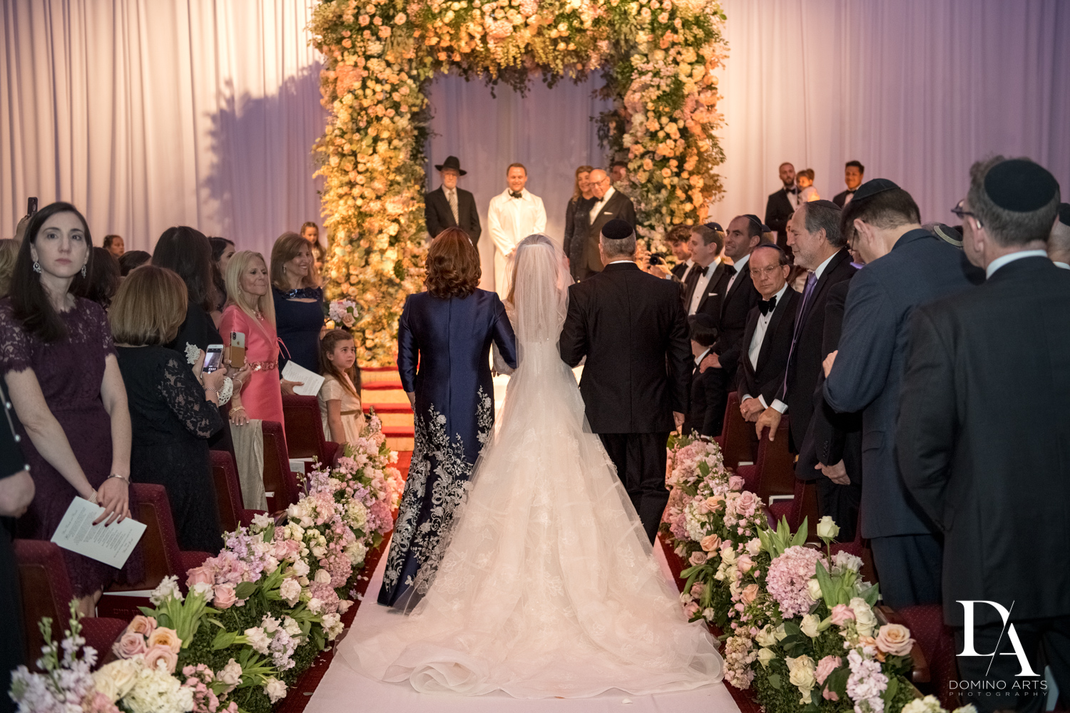Floral aisle and chupah at Lavish Flowers & Crystals Wedding at Aventura Turnberry Jewish Center by Domino Arts Photography