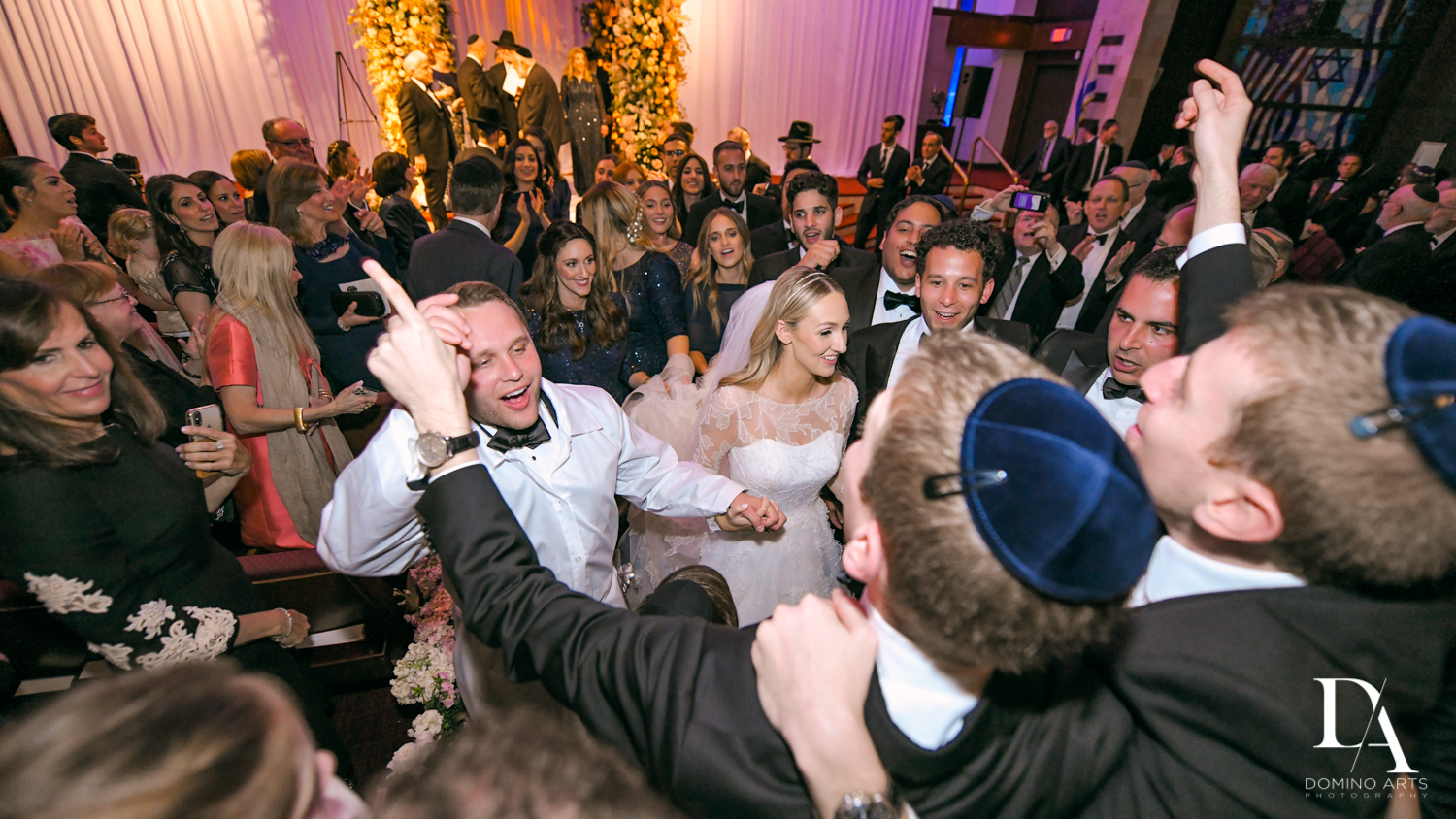 fun dancing at Lavish Flowers & Crystals Wedding at Aventura Turnberry Jewish Center by Domino Arts Photography