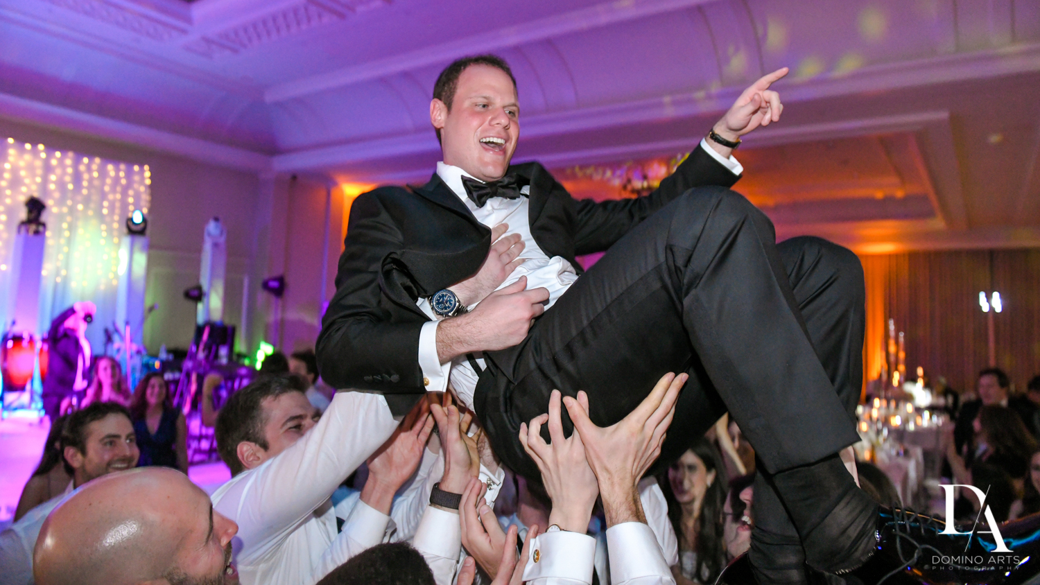 crowd surfing groom at A Ritz Carlton Wedding in Key Biscayne by Domino Arts Photography